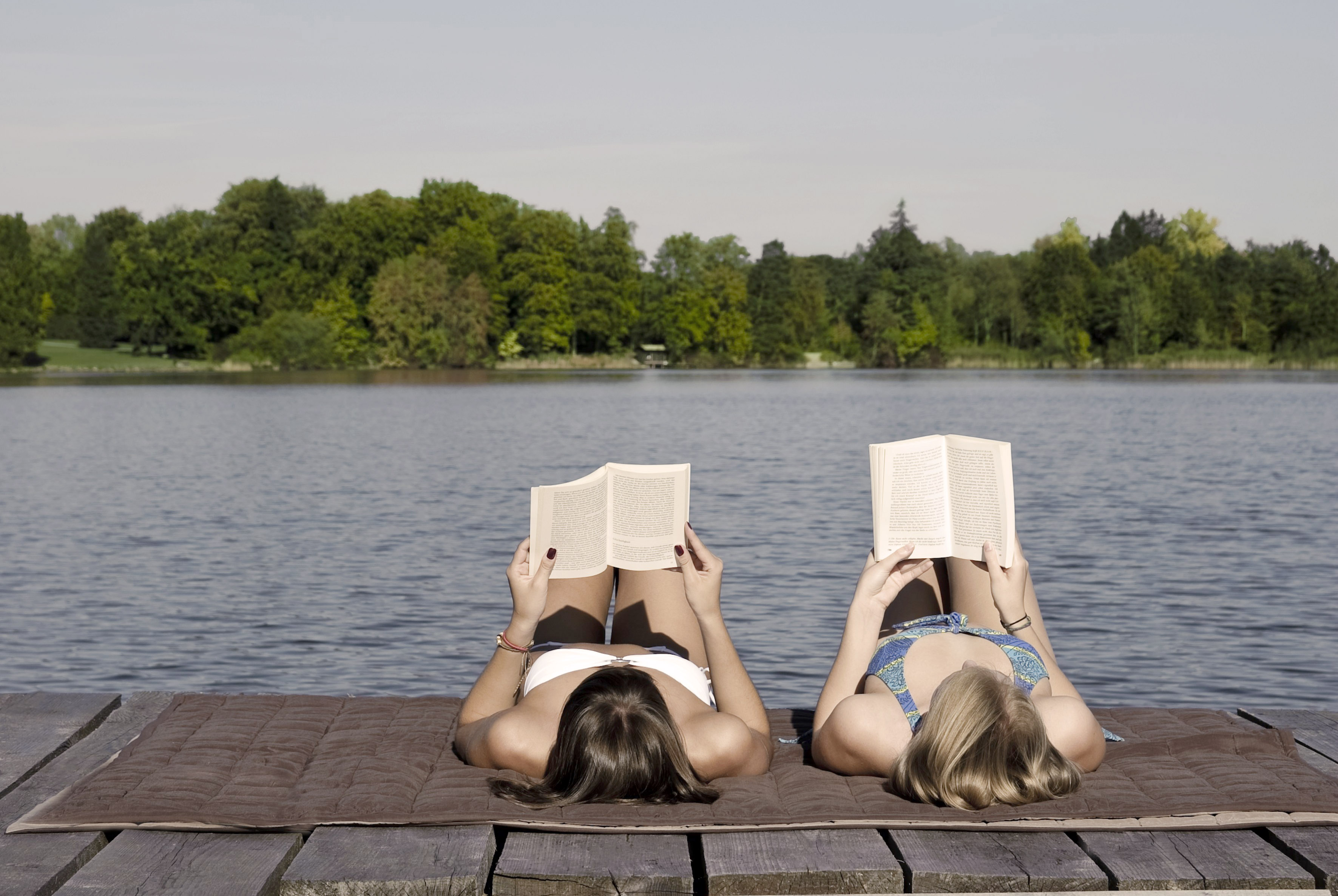 Young women lying on dock reading