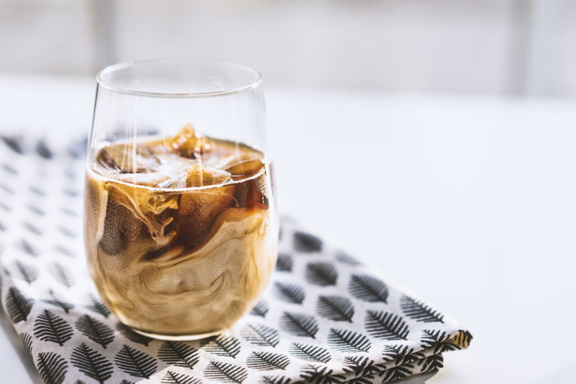 Coffee ice cubes with milk in glass cup on leaf patterned tea towel.