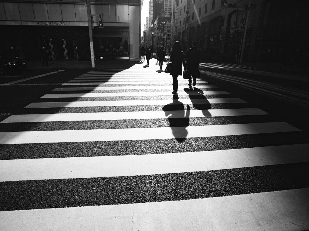velocità a Milano: donna che attraversa la strada sulle strisce pedonali